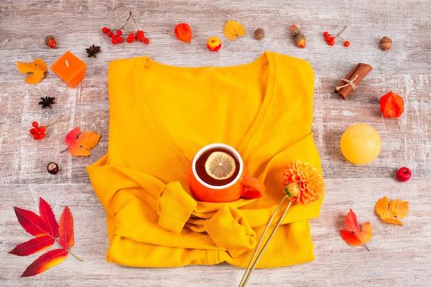 Cárdigan suéter amarillo y taza de té caliente alrededor de hojas secas de vela