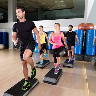 Cardio paso grupo de baile en el entrenamiento de gimnasio de fitness