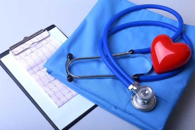 Cardiograma con estetoscopio médico y corazón rojo con bata sobre mesa