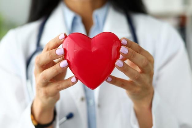 Cardiólogo femenino sosteniendo en brazos corazón de juguete rojo