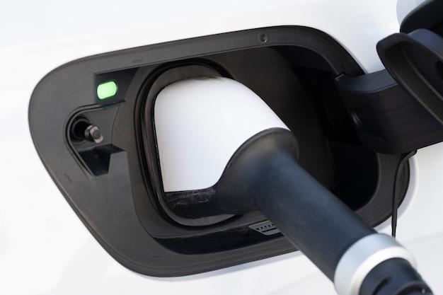 Carga de coche eléctrico blanco en una estación