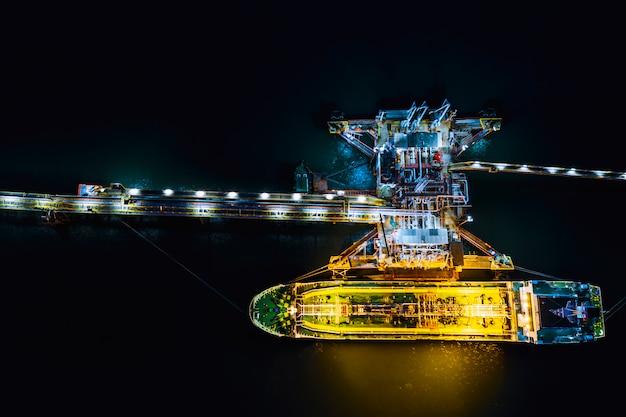 Carga nocturna envío del petrolero cargando carga en la estación de petróleo importación y exportación logística transporte vista superior