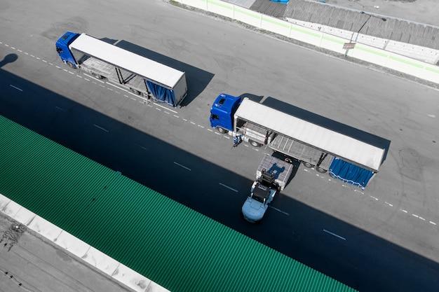 Carga de productos de camiones en la vista superior del centro logístico