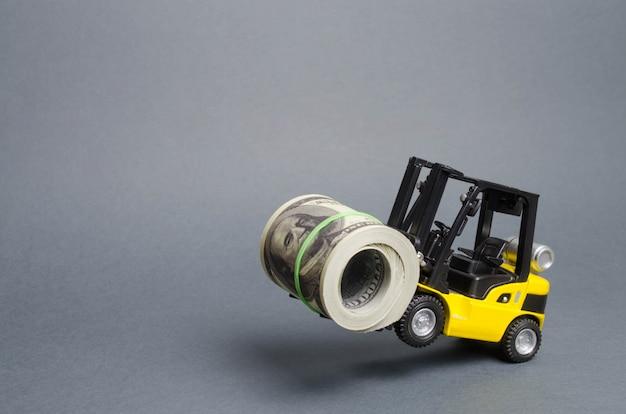 Un cargador amarillo está parado en las ruedas traseras sosteniendo un gran paquete de dólares. concepto de inversión