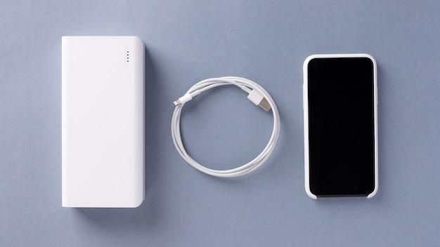 Cargador de banco de energía blanca, cable usb y teléfono inteligente en una caja blanca