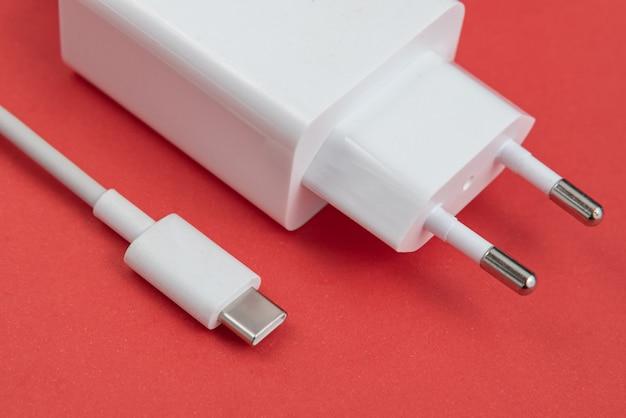 Cargador y cable usb tipo c sobre fondo rojo.