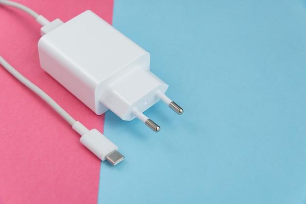 Cargador y cable usb tipo c sobre fondo rosa y azul