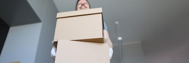 Un cargador en una habitación vacía sostiene un cartón.