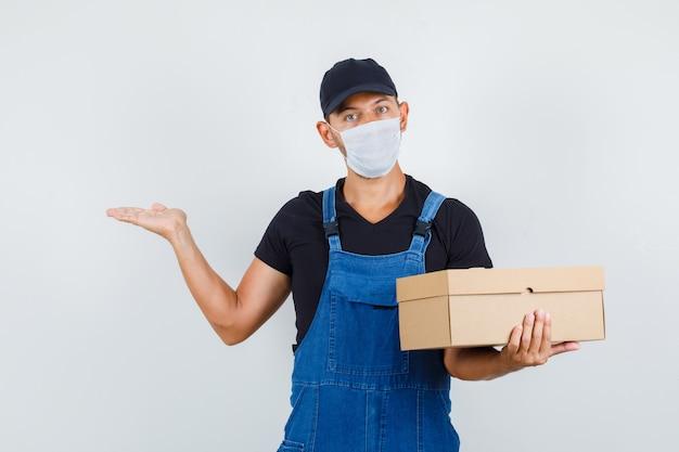Cargador joven que sostiene la caja de cartón con la palma extendida a un lado en uniforme, vista frontal de la máscara.