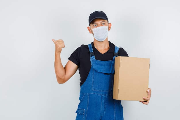 Cargador joven sosteniendo una caja de cartón mientras apunta hacia atrás en uniforme, vista frontal de la máscara.