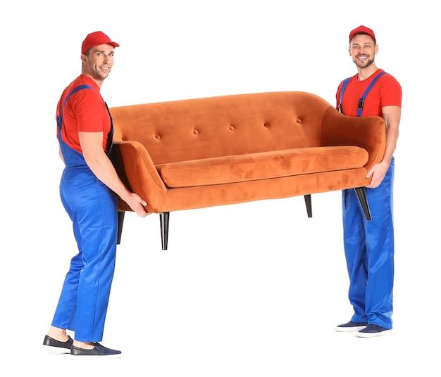 Cargadores que transportan muebles contra un blanco