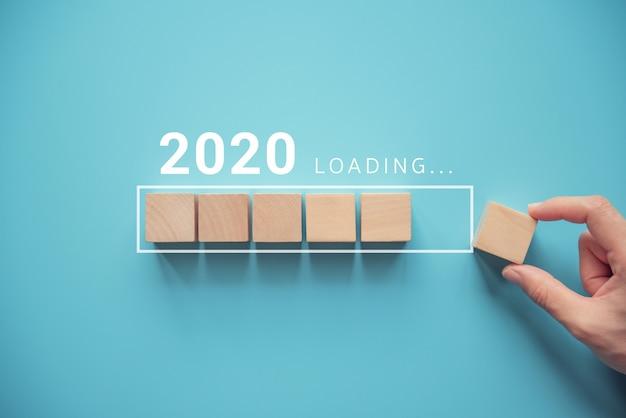 Cargando el nuevo año 2020 con la mano poniendo el cubo de madera en la barra de progreso.
