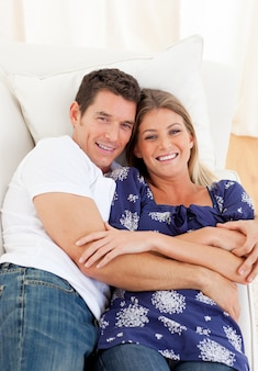 Cariñosa pareja acostada en el sofá