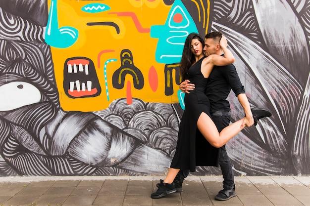 Cariñosa pareja bailando frente a la pared de graffiti