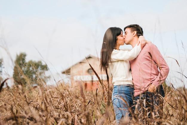 Cariñosa pareja joven de pie besos