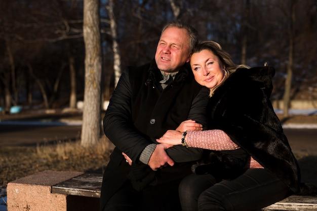 Cariñosa pareja senior sentado en la banca