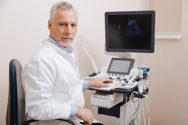 Carismático y agradable médico anciano que trabaja en el hospital y utiliza una sonda lineal ultrasónica mientras espera al paciente