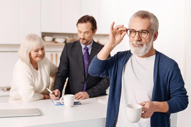 Carismático anciano con estilo confiado de pie y sosteniendo la taza de té mientras su esposa firma documentos con el agente inmobiliario