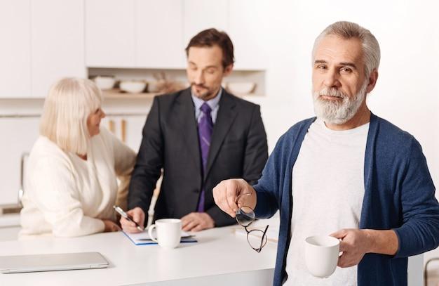Carismático anciano pacífico de pie y sosteniendo la taza de té mientras su esposa conversa con un agente inmobiliario