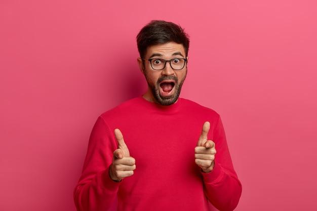 Carismático excitado hombre sin afeitar apunta directamente