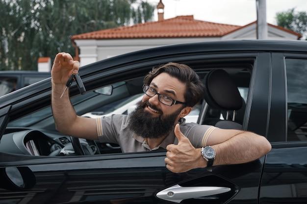 Carismático hombre sosteniendo las llaves del auto mostrando los pulgares para arriba