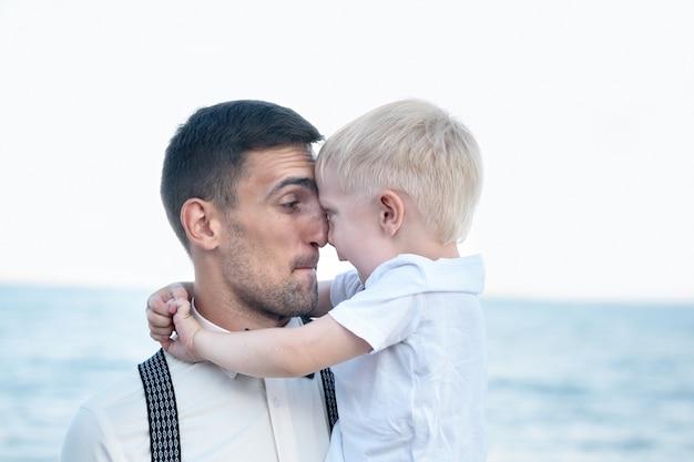 Carismático joven padre con un hijo pequeño. niño abraza a papi. padre amor paternidad.