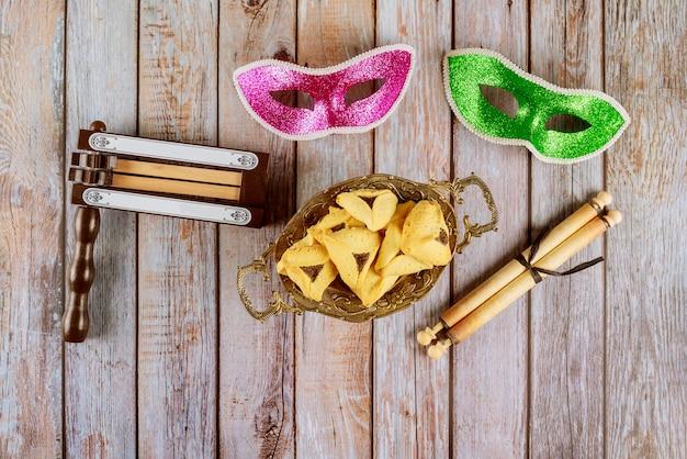 Carnaval con máscara y matraca galletas hamantaschen fiesta judía de purim