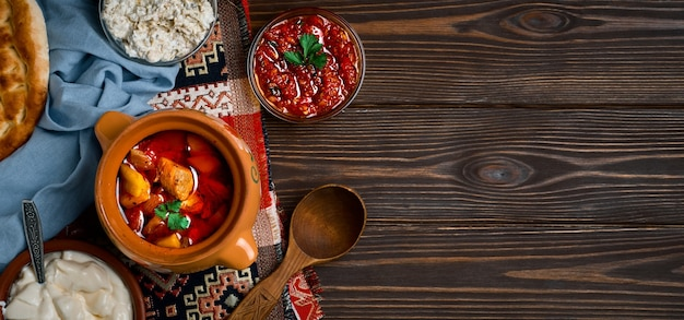 Carne al horno en cazuela de barro, o una cazuela tradicional, un guiso con verduras y carne cocida al horno. plato de comida turca y balcánica u oriental, plano con espacio de copia