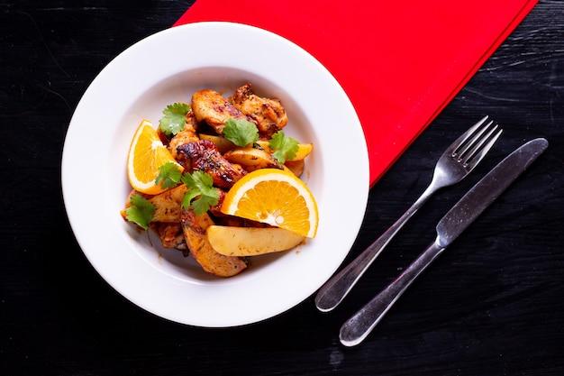 Carne al horno con patatas y naranja, plato de restaurante en la vista superior de la mesa