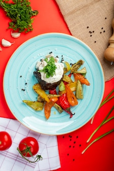 Carne asada con crema agria y verduras.