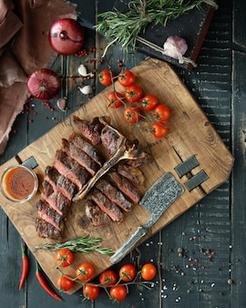 Carne asada en un hueso y verduras frescas en una tabla de cortar de madera en estilo rústico