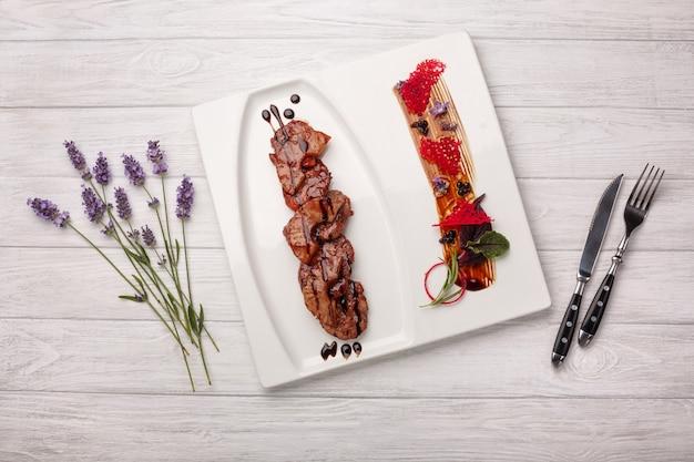 Carne asada con piña en salsa balsámica sobre una tabla de madera blanca