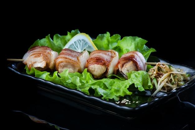 Carne en brochetas de madera, carne de cerdo, pollo, pescado, vieira, carne de res, camarones en un plato negro sobre una pared negra.