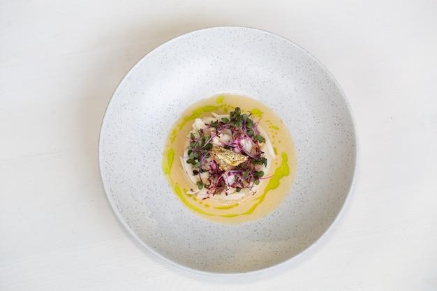 Carne de cangrejo en sopa de crema de coco y micro greens sobre fondo de hormigón gris vista superior espacio de copia h ...
