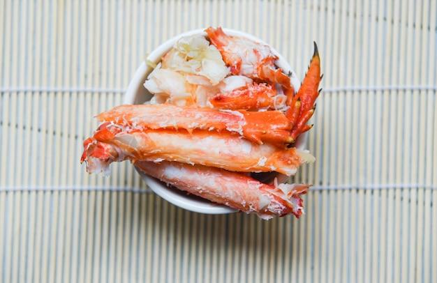 Carne de cangrejo en una taza en la vista superior de madera backgrond - cangrejo rojo hokkaido