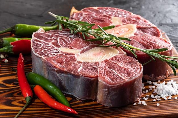 Carne carne ternera caña en rodajas carne en tabla de cortar de madera oscura.