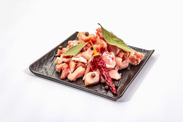 Carne de cerdo cruda en cubitos con laurel seco y ají