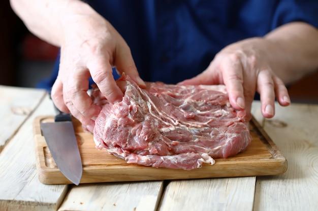 Carne de cerdo cruda sobre una tabla para cortar.