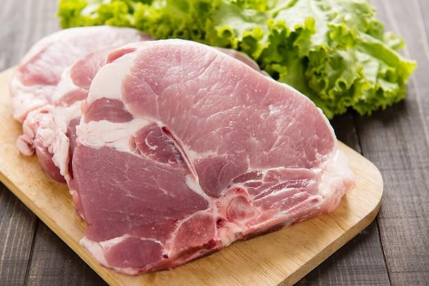 Carne de cerdo cruda en tabla de cortar y verduras en la mesa de madera