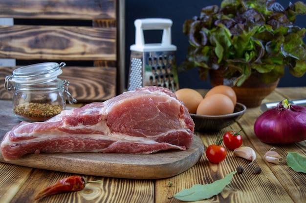 Carne de cerdo cruda en una tabla de cortar y verduras