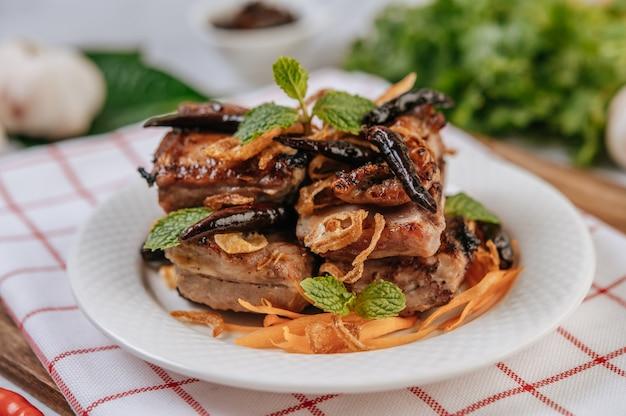 Carne de cerdo frita con chile frito cebolla frita y menta en un plato blanco.