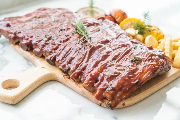 Carne de cerdo a la parrilla con salsa de barbacoa y patatas fritas vegetales y frech en tabla de cortar de madera