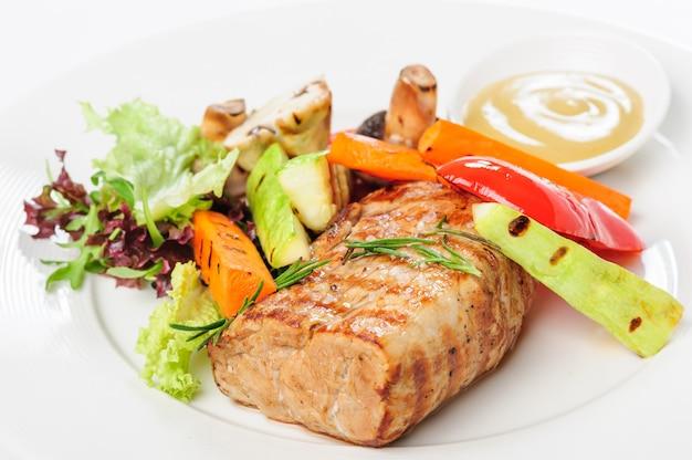 Carne de cerdo a la parrilla y verduras en placa