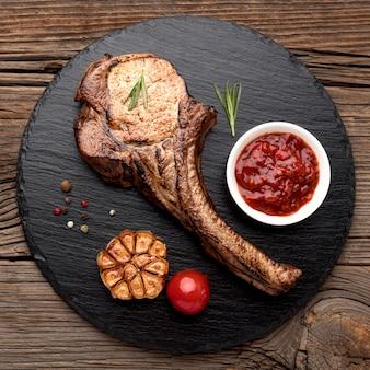 Carne cocida con salsa sobre tabla de madera