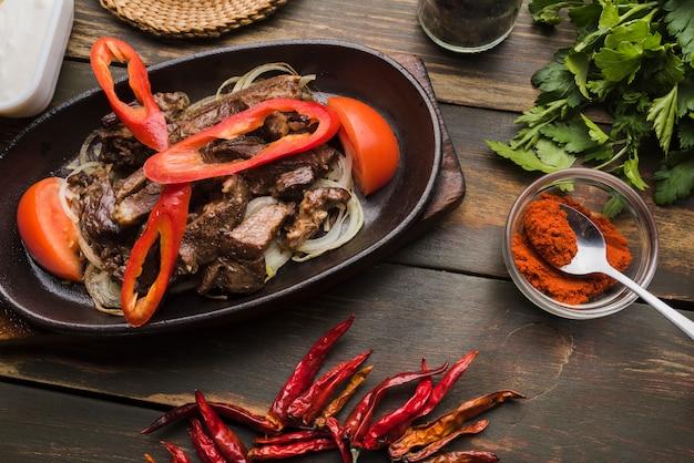 Carne cocida con tomates y pimientos en sartén