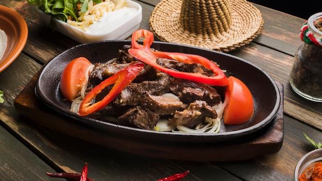 Carne cocida con verduras y diferentes aperitivos.