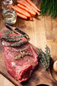 Carne cruda de la carnicería aliñada con romero, sal y pimienta junto con aceite de oliva virgen y zanahoria. vegetales verdes.