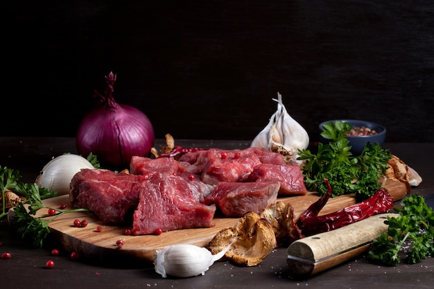 Carne cruda fresca; botella de vino y verduras orgánicas de otoño estacionales sobre tabla de madera lista para cocinar