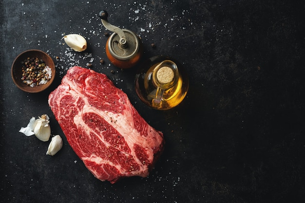 Carne cruda fresca con especias y sal en rústico oscuro.