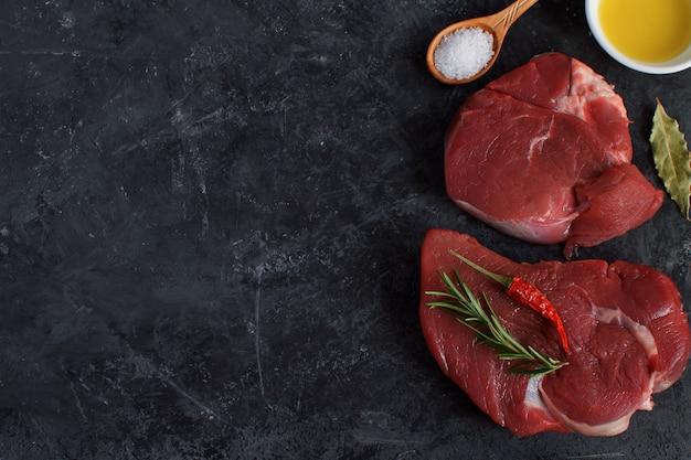 Carne cruda fresca filete de ternera aceite de oliva especias sal cuchara de madera ají romero concepto de cocina